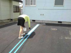 駐車場のラインを引く女性